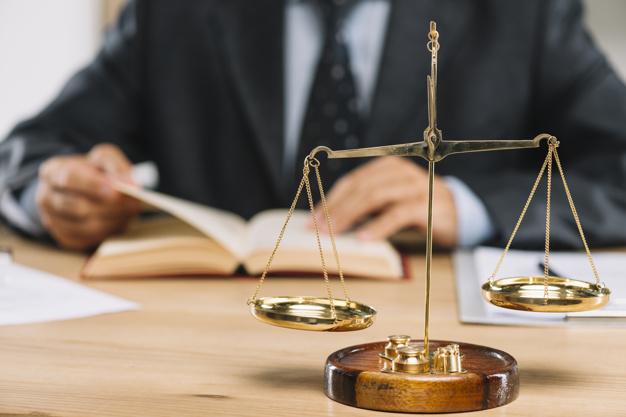 escala-de-justica-de-ouro-na-frente-do-livro-de-leitura-de-advogado-na-mesa_23-2147898544
