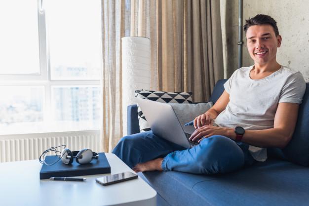 jovem-atraente-sentado-no-sofa-em-casa-trabalhando-em-um-laptop-online-usando-a-internet_285396-1709