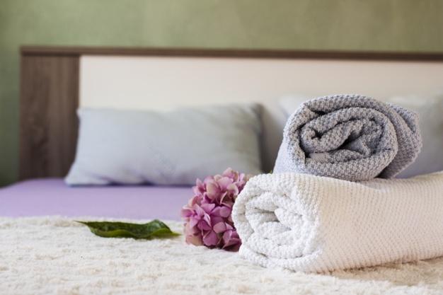 arranjo-com-toalhas-e-flores-na-cama_23-2148295964